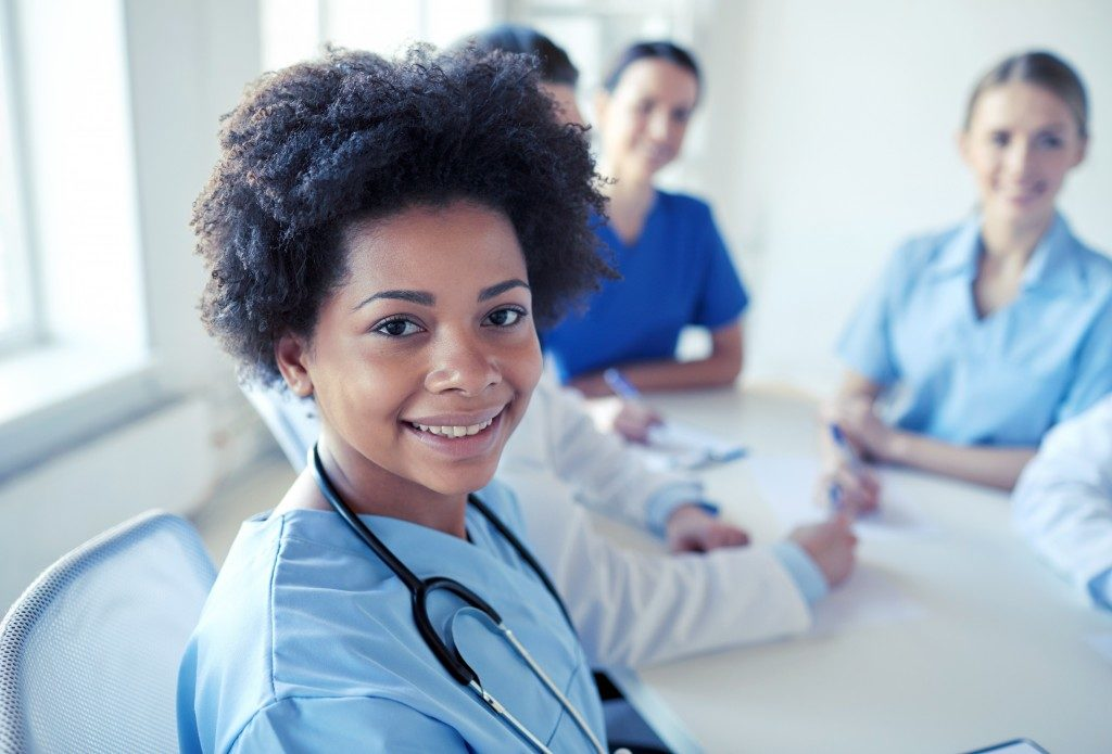 Health care people together with woman smiling to the camera