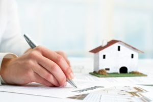 a woman filling up a document for a real estate asset