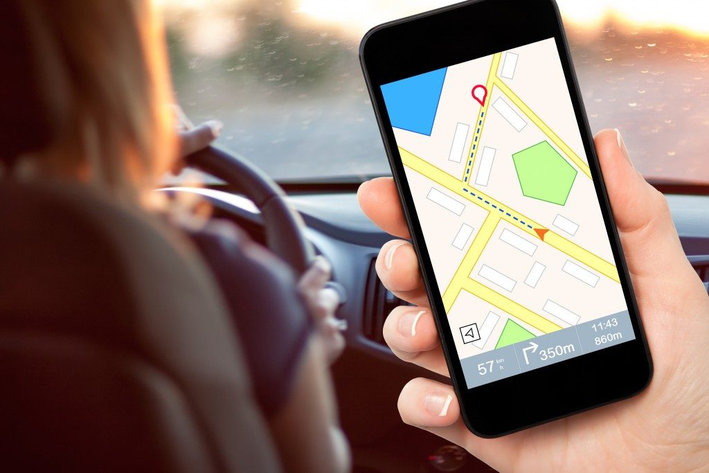 female hand holding a phone with interface navigator on a screen on a background woman driving a car
