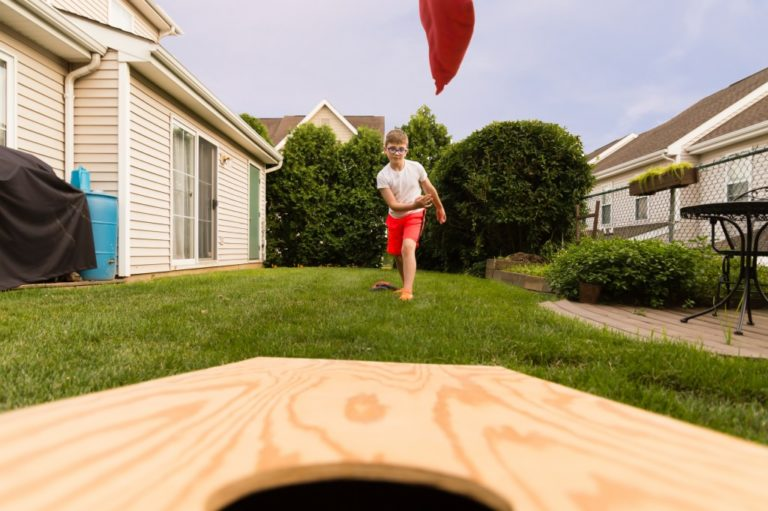 Kid playing cornhole