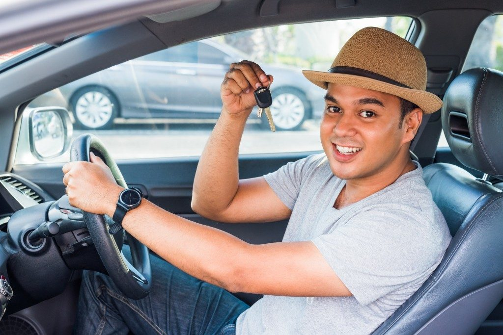 Man inside car showing car keys