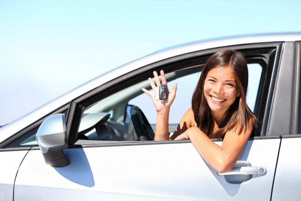 Woman inside car while holding car keys