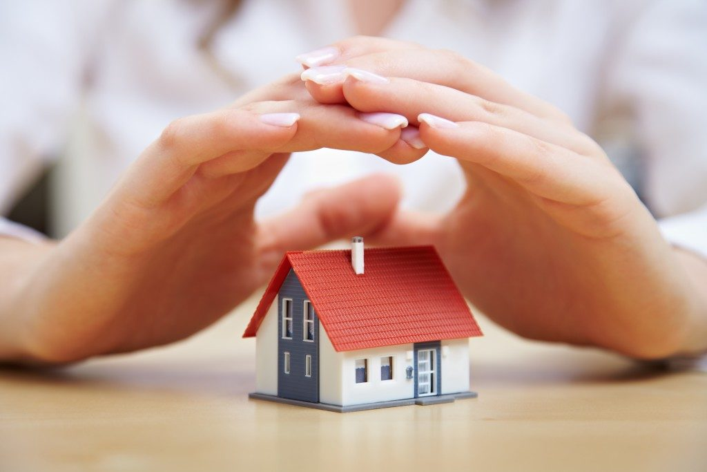 person's hand covering a miniature house