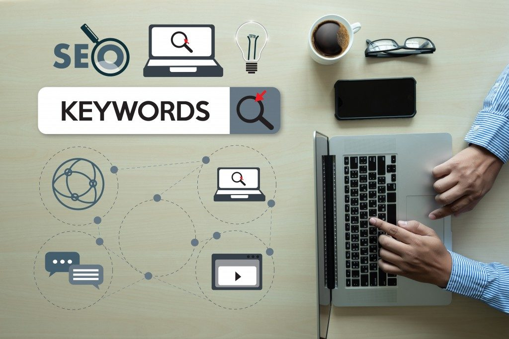 top view of keyword related vitual icons and a man using laptop