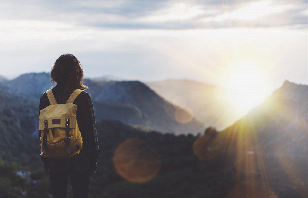 girl with backpack enjoying sunset