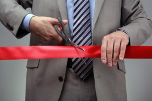 cutting red ribbon for launch