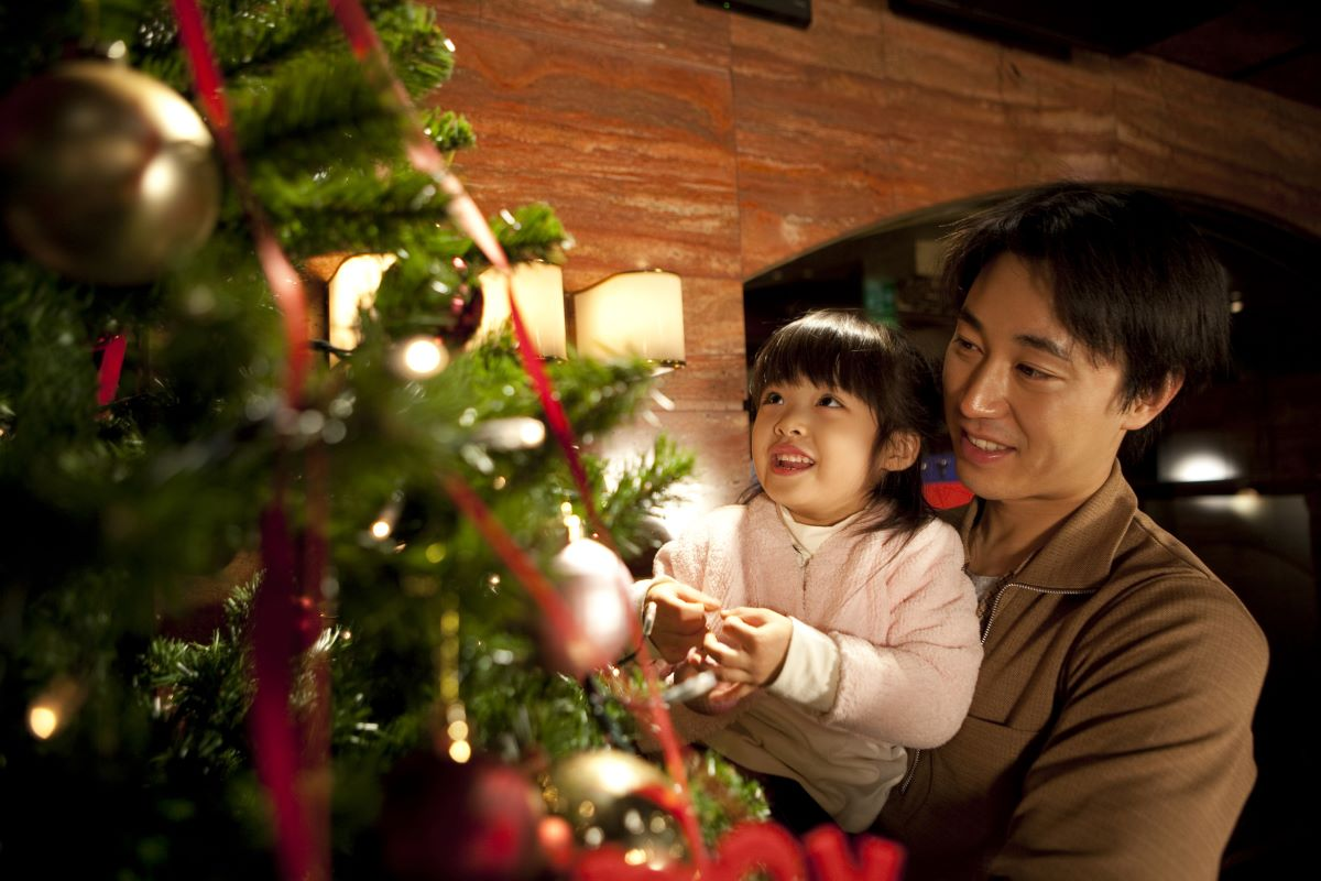 parent and child setting up christmas tree