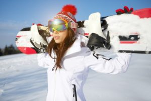woman holding snowboard behind her head
