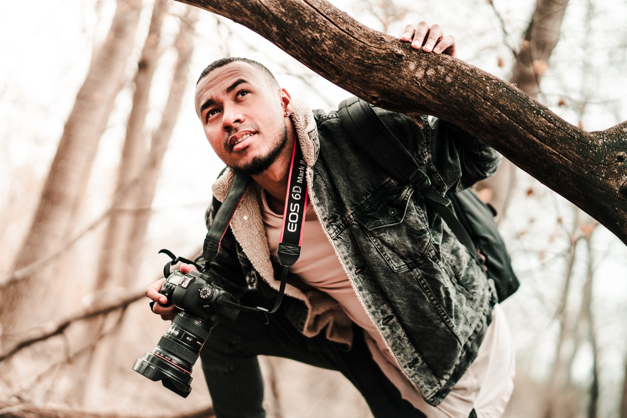 man holding camera while holding on to tree branch