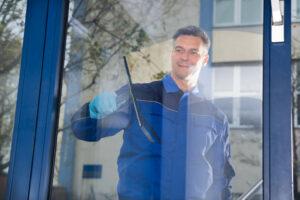 man cleaning window glass pane